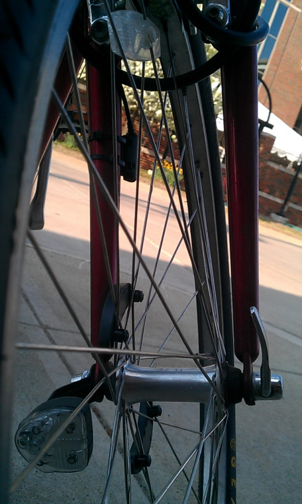 close up of my bike's front wheel while parked in the bike rack